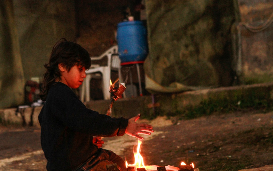 A child burns wood to heat himself in the streets of rebel-held Aleppo.