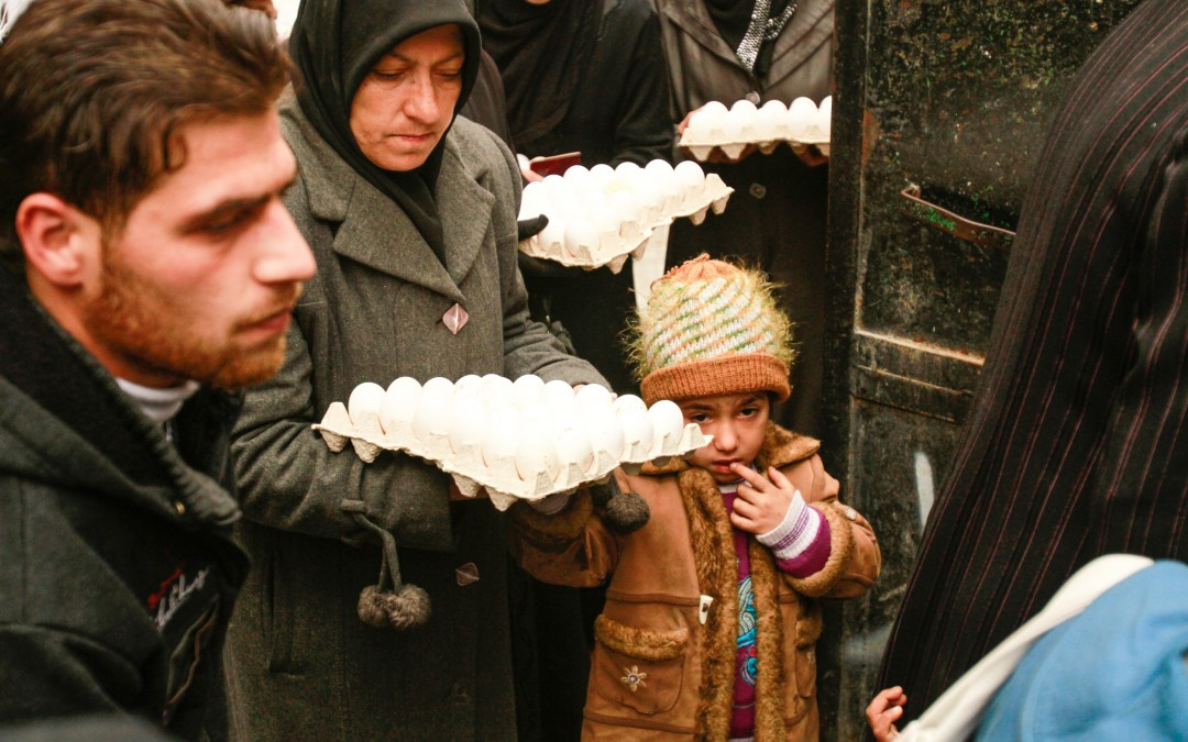 People wait in line for food to be distributed. There are 13.5 million people currently in need of humanitarian assistance in Syria, according to the UN's World Food Programme.
