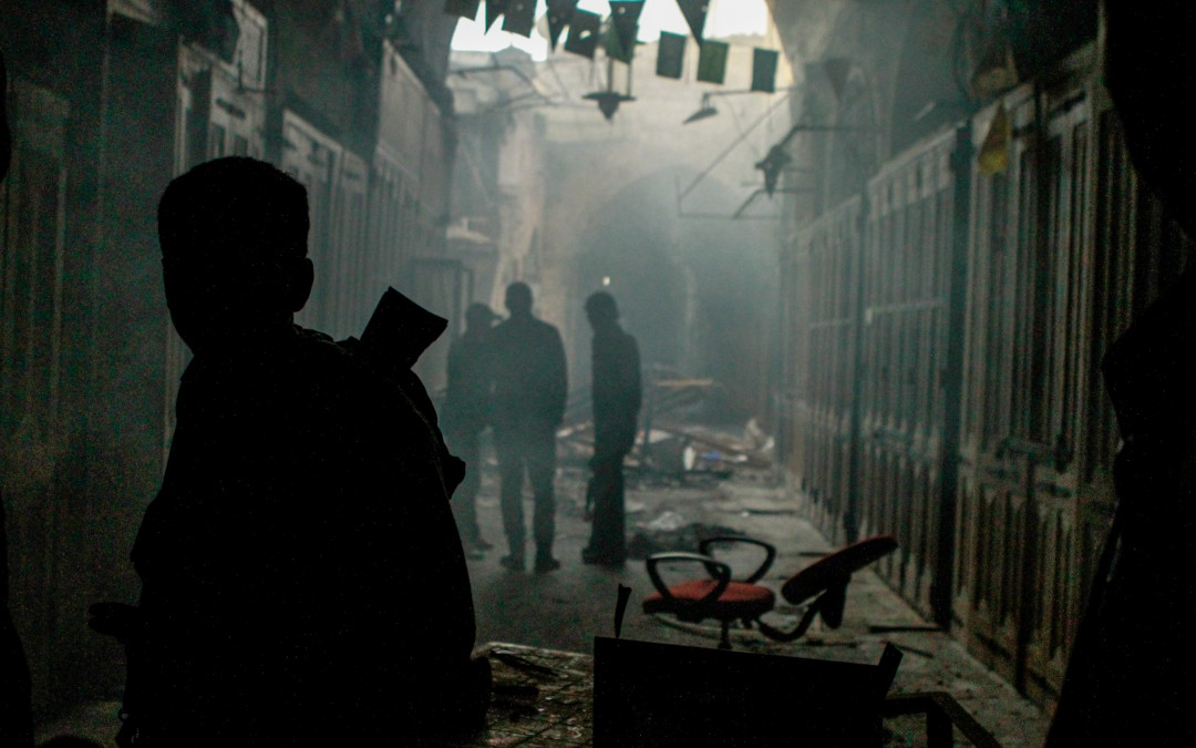 Free Syrian Army fighters walk through a destroyed market in the