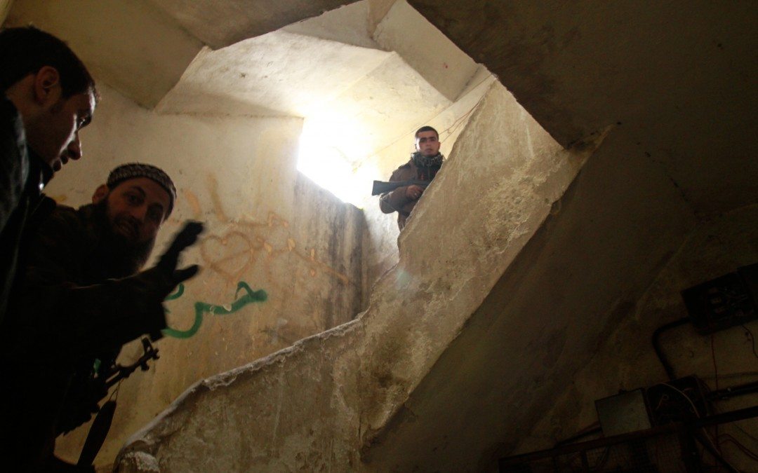 Rebel fighters take position in an abandoned house at the frontline, in Aleppo.